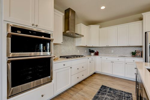 White kitchen with herringbone backsplash in a new house